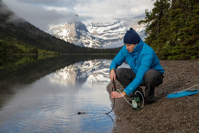 Visitor filtering water at Cosley Lake in Glacier National Park