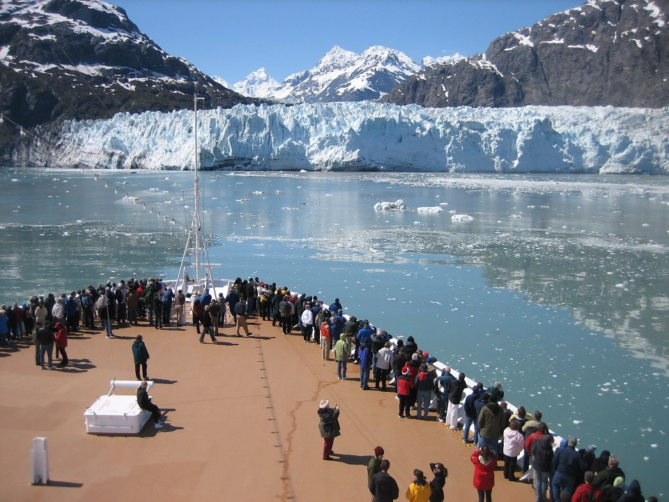 Crowd of people on a cruise ship deck approaching a glacier