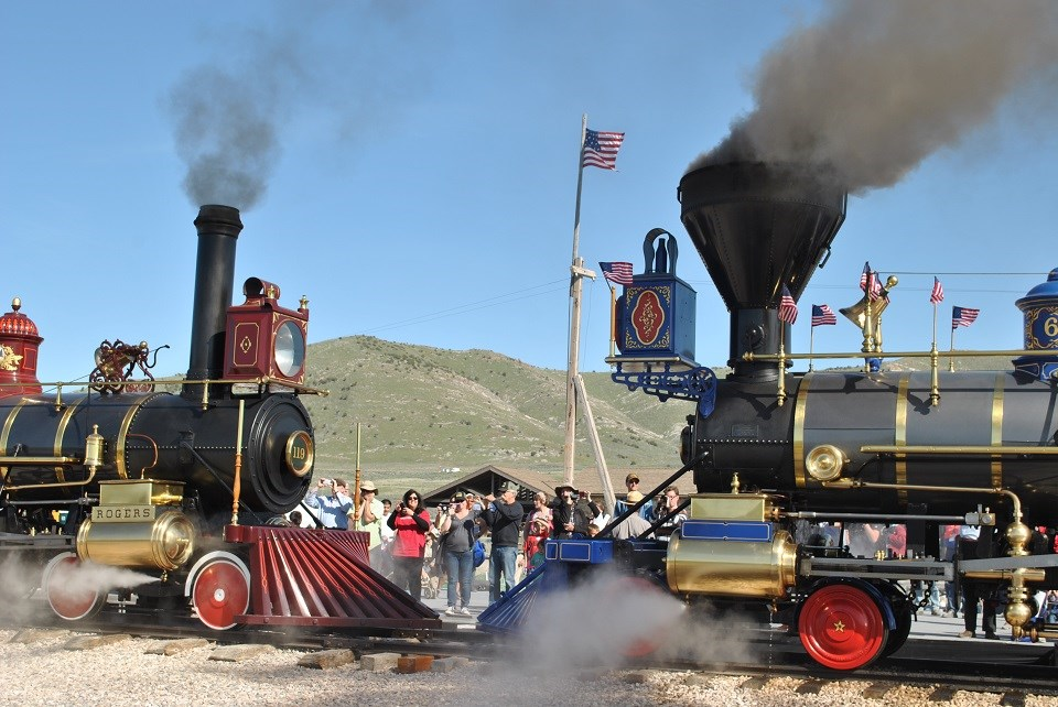 Two steam engines facing each other on a railroad track with a crowd watching