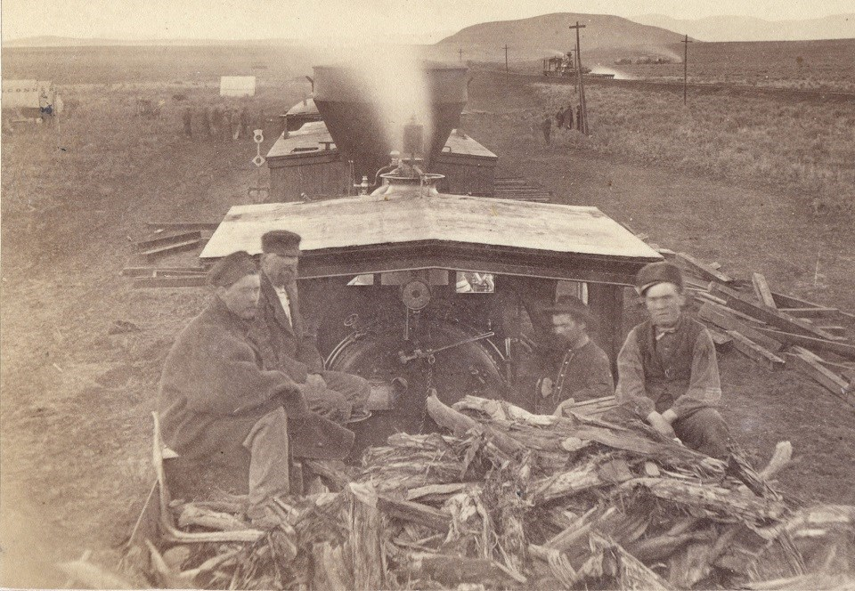 Black and white photo of railroad workers sitting on top of wood piled in a train cart