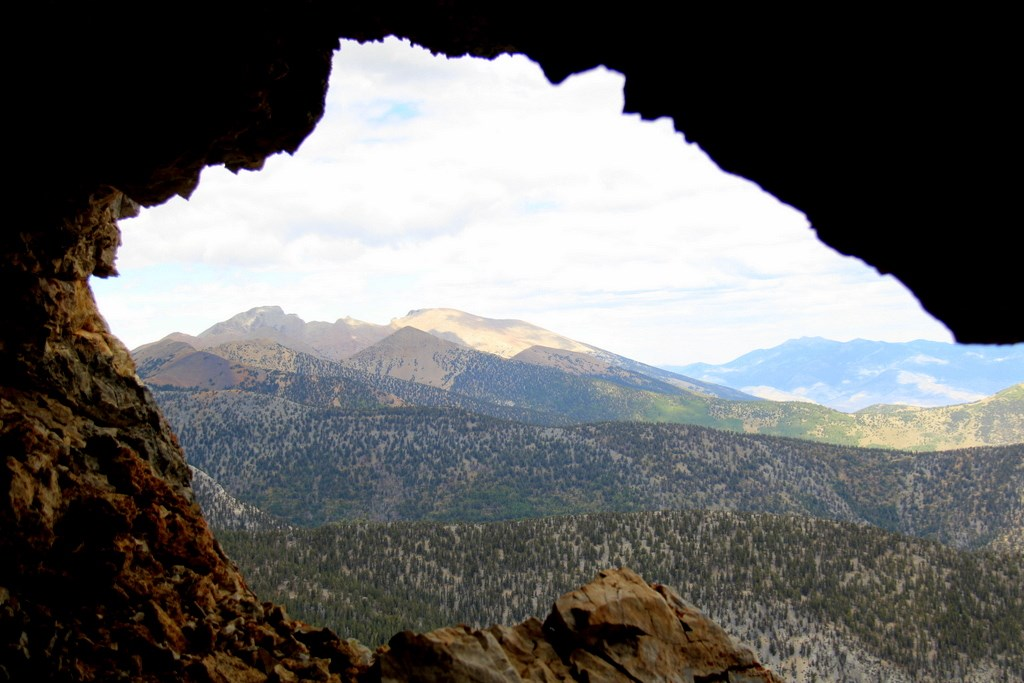 view out of cave opening, mountains and trees