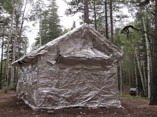 Cabin near forest fully wrapped in silver reflective material.