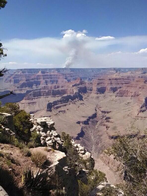 A plume of smoke in the distance beyond the Grand Canyon rises into the blue sky.