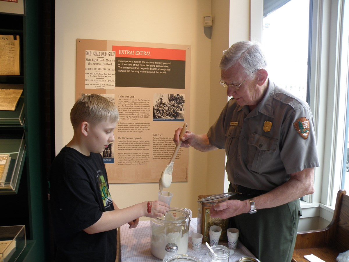 Ranger mixing sourdough in a demonstration with a child