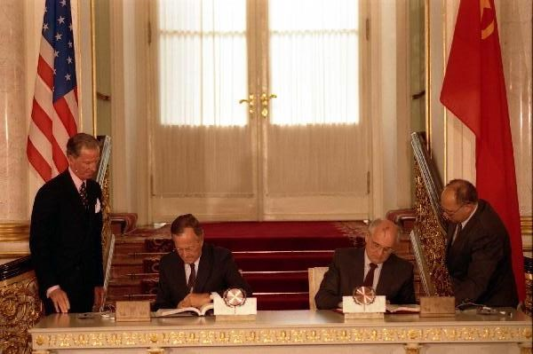 Presidents Bush and Gorbachev sign a treaty while seated at a table.