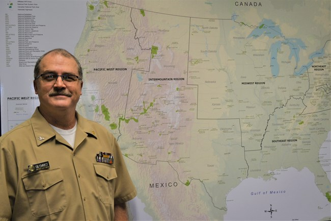 Headshot of Tracy Gilchrist standing in front of a map of the U.S.
