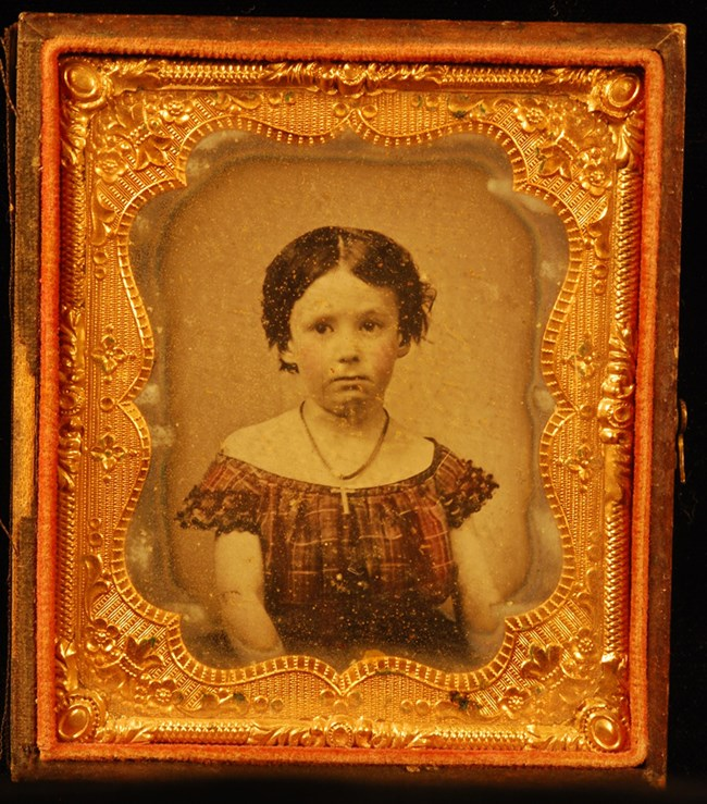 Tintype photograph of girl wearing a checkered dress and a cross necklace