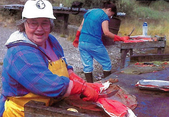 An older woman wearing a white ball-cap, blue jacket and waterproof, yellow apron cutting fish on a wet wooden table.