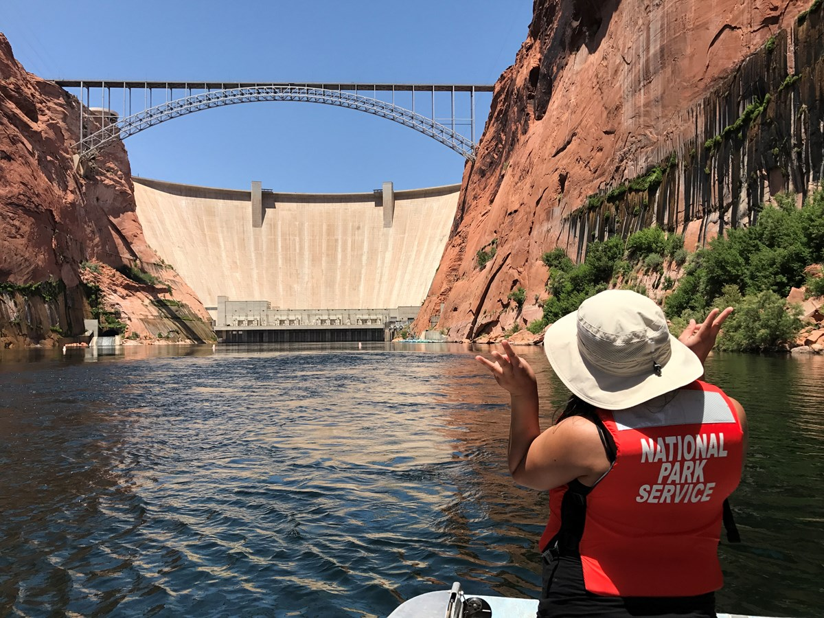 back of woman wearing a red life vest in foreground, lake in the midground, and a large dam in the background
