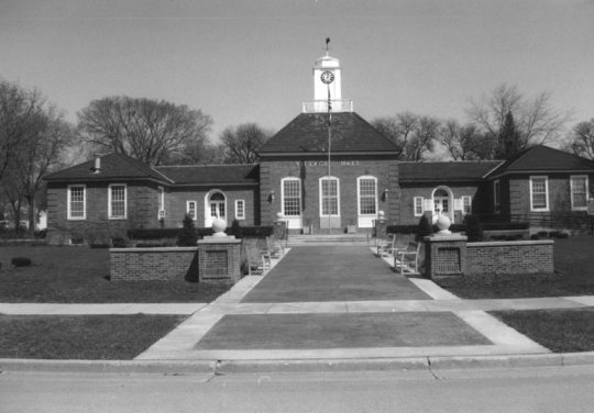 B&W photo of a brick building with a small court and flagpole in front.
