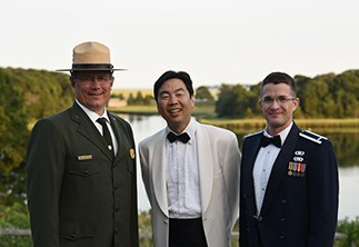 Three men stand outdoors in front of a large pond ringed with trees. From left to right: A man wearing a green National Park Service dress uniform, a man in a tuxedo with a white coat, and a man wearing a blue United States Air Force dress uniform.