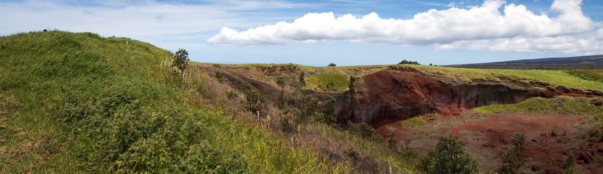 Green hill with red volcanic soil exposed under blue sky with clouds