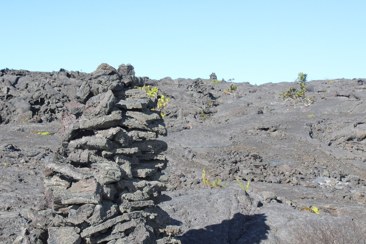 large stack of gray rocks in a cone shape on a lava field