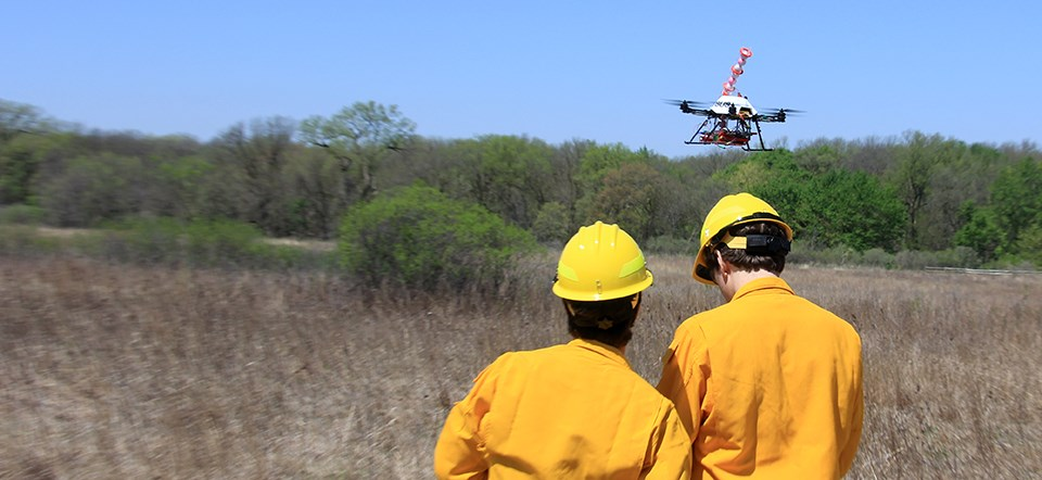 An unmanned aircraft hovers above a field while two men in firefighting gear stand nearby.