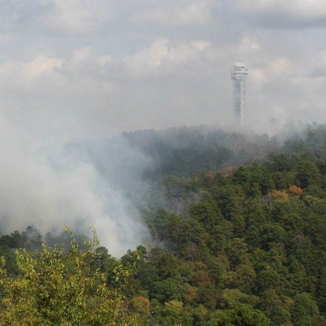 Smoke from a prescribed fire rises. The mountain observatory tower is at the top of the mountain.