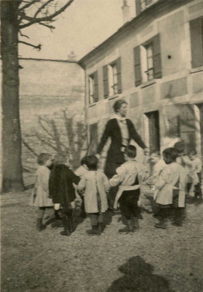 Woman and about nine small boys hold hands in a ring in front of building.