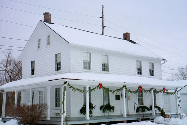 Exterior of a white, wooden house in winter