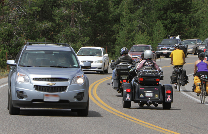 Cars pass by motorcycles and bicyclists