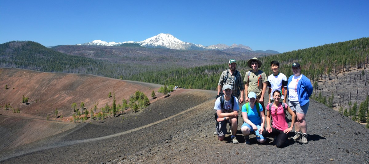 A group of seven people pose for a photo on the crater of a cinder cone volcano; a snow-capped volcano rises in the distance