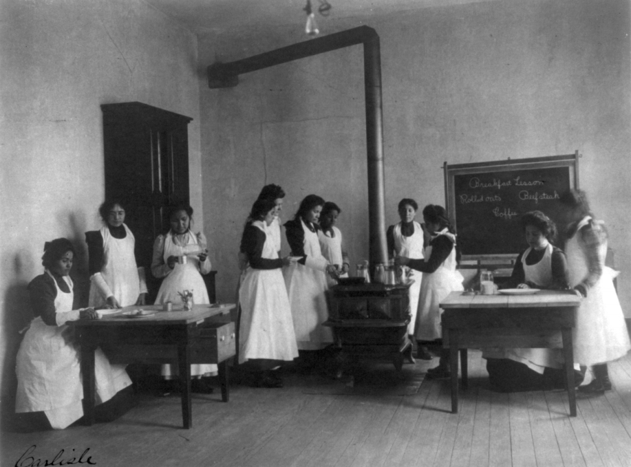Girls cooking. They are all wearing aprons.