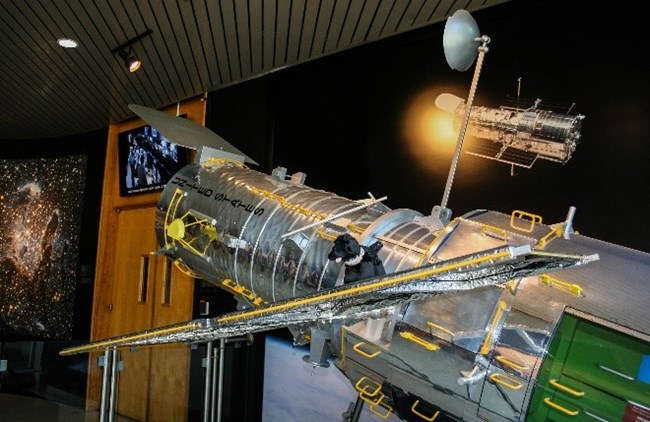 toy dog on model of the HUbble Space Telescope