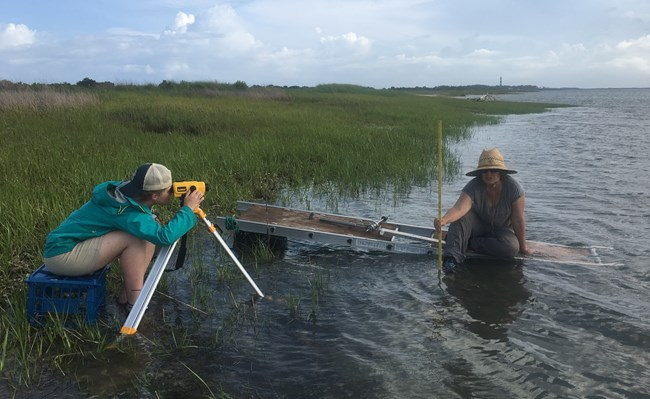 Anna Hilting holds a measuring rod sitting on a platform in the water and Elaina Sherman collects elevation data.