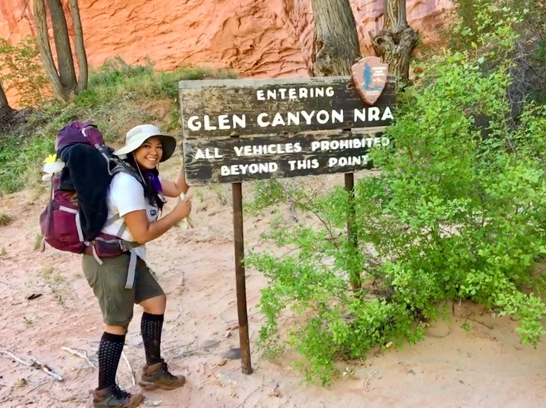 "young woman dressed in hiking clothing and gear standing next to a sign that says ""Entering Glen Canyon NRA"""