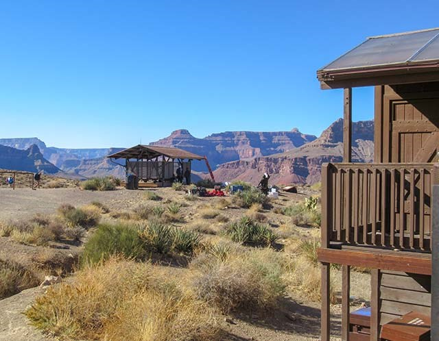 two buildings, an open-sided shade structure, and a composting toilet in a desert environment, with colorful cliffs in the distance