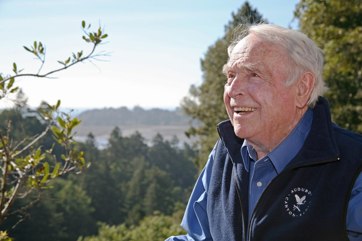 Portrait of a smiling older man outside in the sun, wearing an Audubon Canyon Ranch vest.