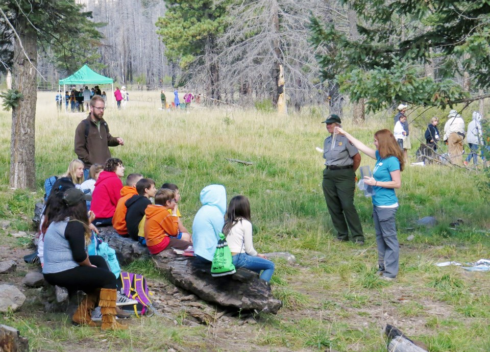 Staff talk to groups of students at an environmental education program