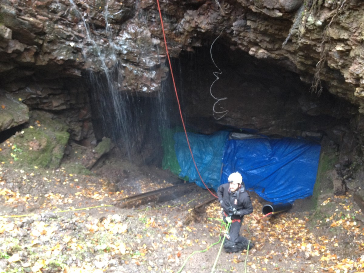 A man with safety gear underneath a rock overhang with water tripping off of it