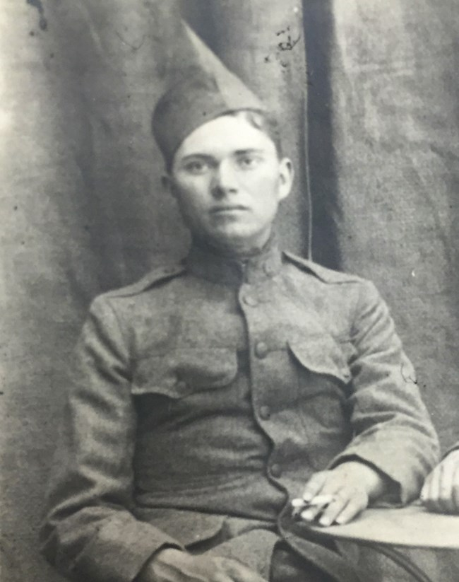 Photo of man in private's uniform sitting at a table