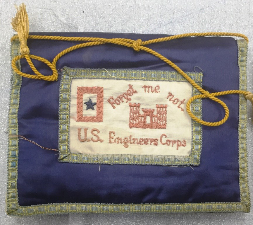 "Silk envelope with blue border. Embroidered text reads ""Forget me not, U.S. Engineers Corps."" Also embroidered is an image of a castle and a blue star with red border."