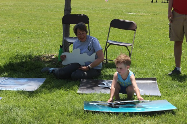 A young boy plays a game, placing a cut out of a shark over a picture of a shark while a woman sits on the ground behind him smiling