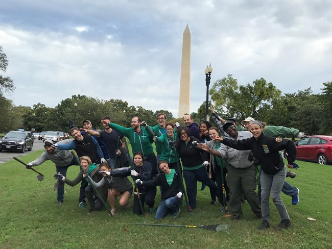 Volunteers and National Park Service employees laugh and strike a pose in front of the Washington Monument