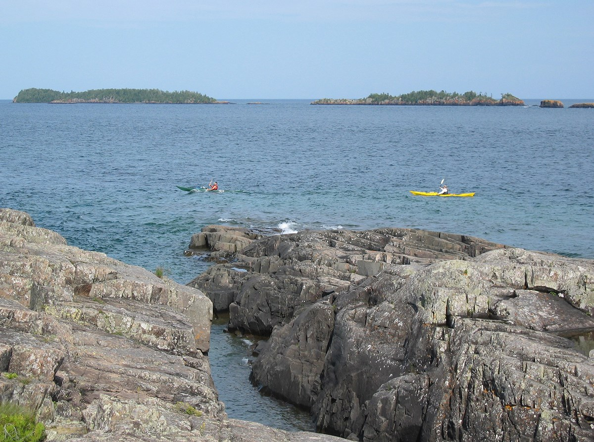 rocky shoreline and open water with 2 kayaks in view