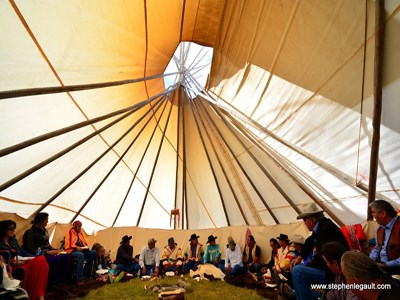 Members of the Inter-tribal Buffalo Council sit together inside a large teepee