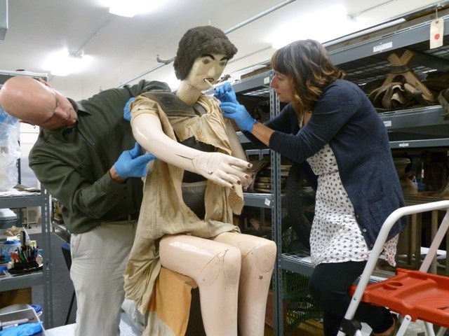 Two employees carefully removing the clothes of a mannequin