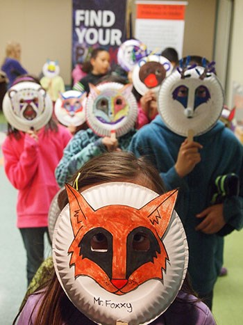 Kids hold up animal masks that they made