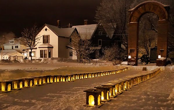 Rows of lit luminaries line a path to the Italian Hall memorial