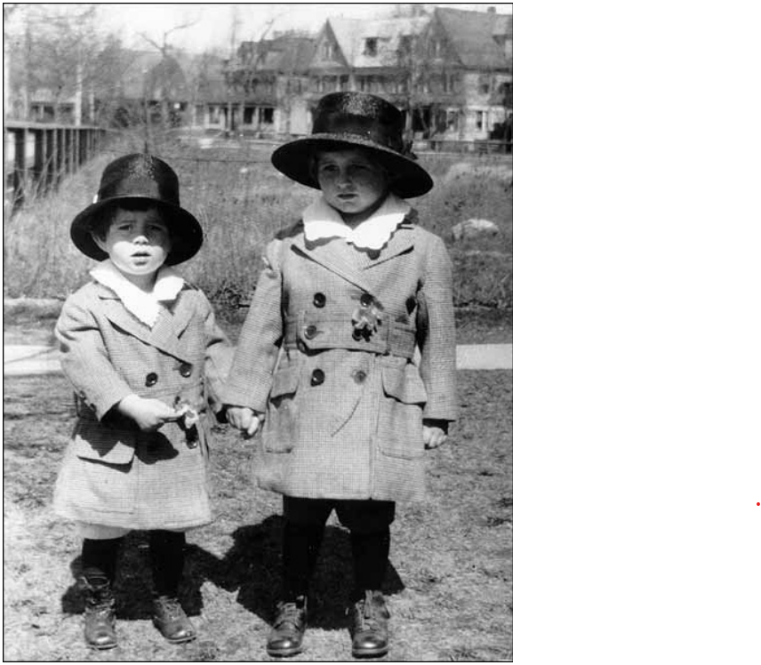 Two young boys standing outside in matching clothing