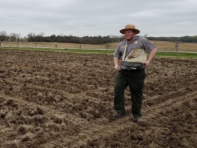 Ranger walks in tilled field spreading seed with a vintage hand cranked seed spreader.