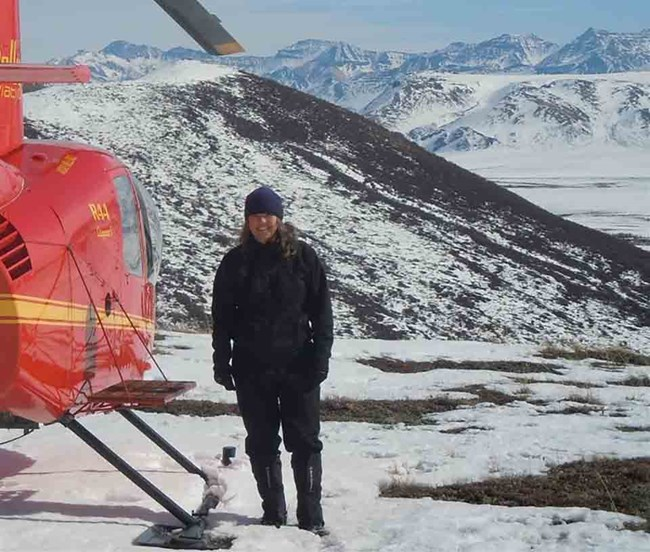 Wildlife Biologist Judy Putera stands by a helicopter in the winter.