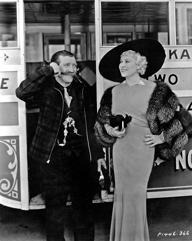 Martin Itjen smiling and standing next to Mae West