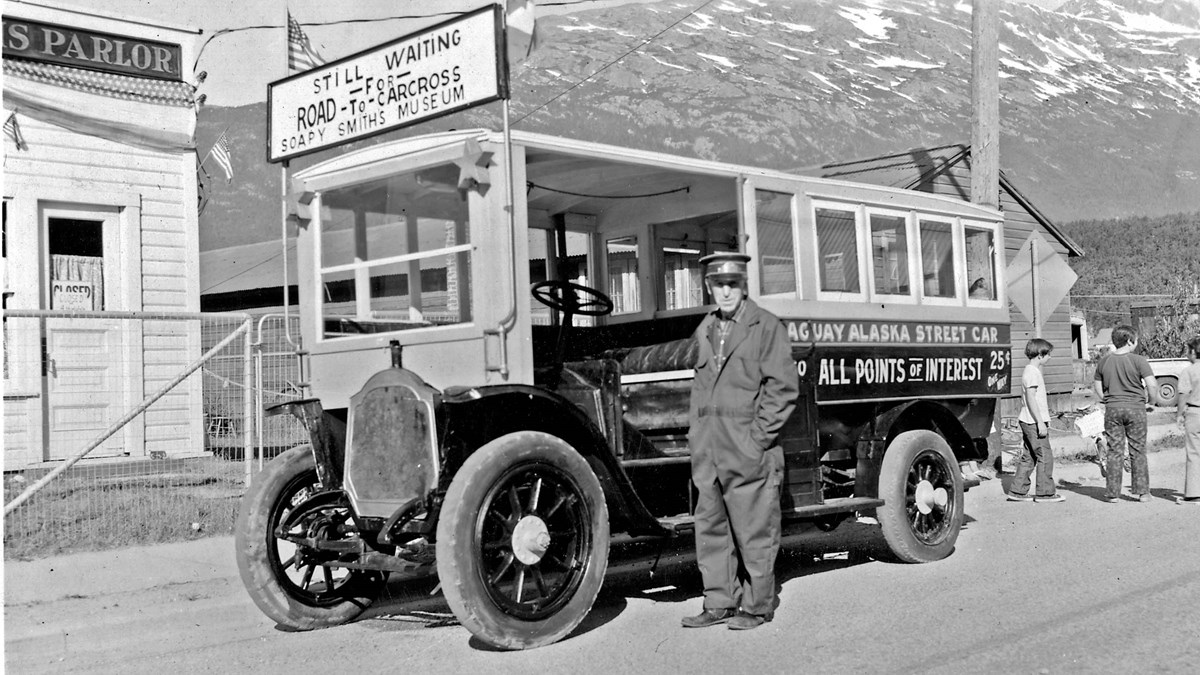 George Rapuzzi stands in front of a street car with a mountain in the background