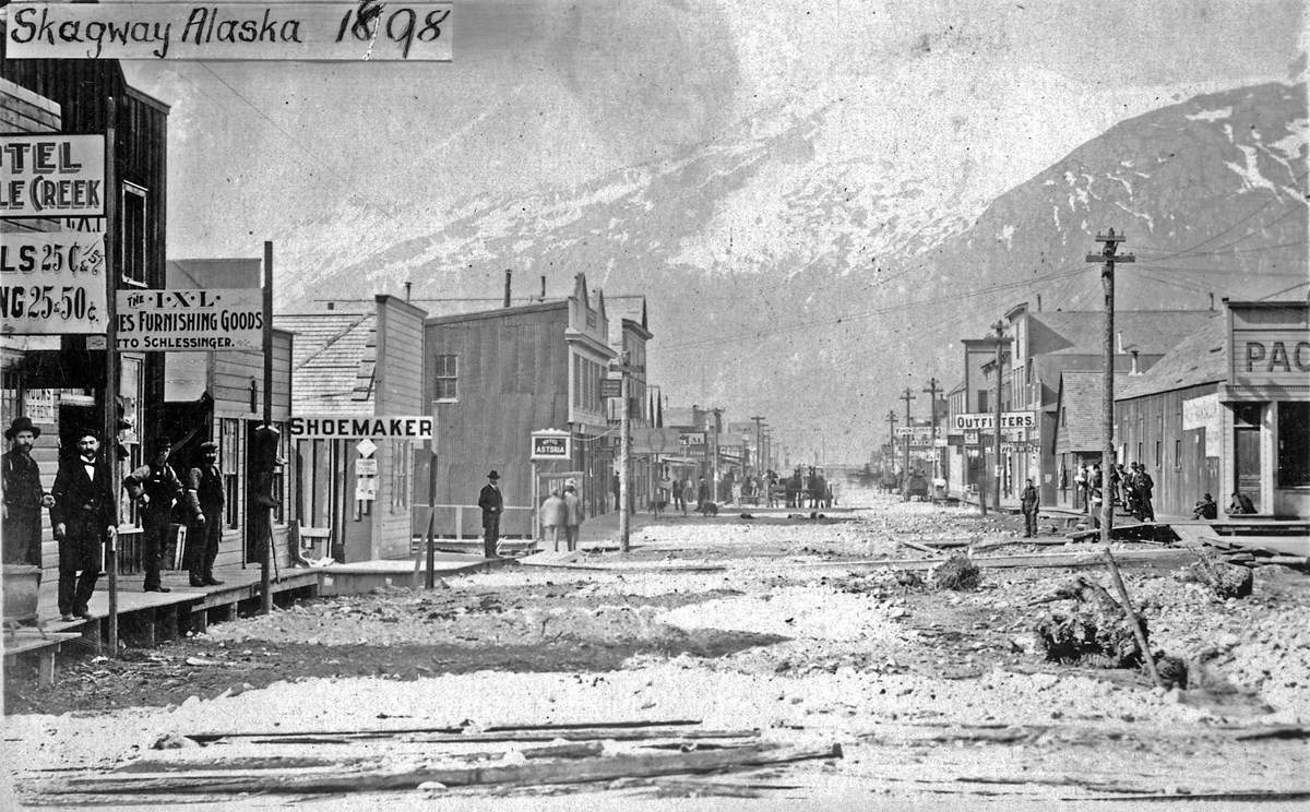 A street scene. Stores lining the left and right of the street with mountains in the background.