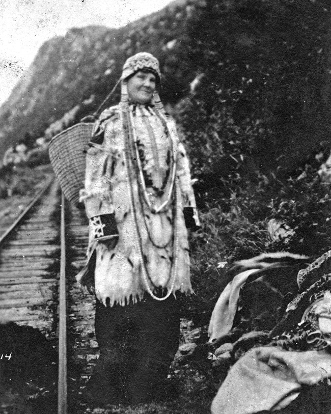 A woman standing with native decorative clothing along a railroad track