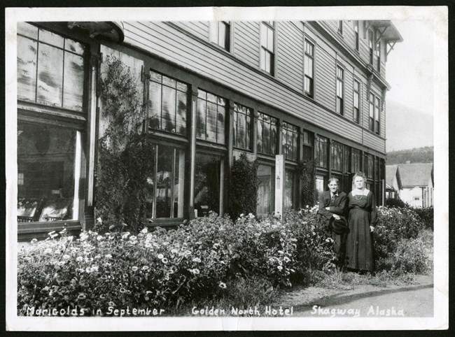 Two residents stand next to their marigolds outside the Gold North Hotel.