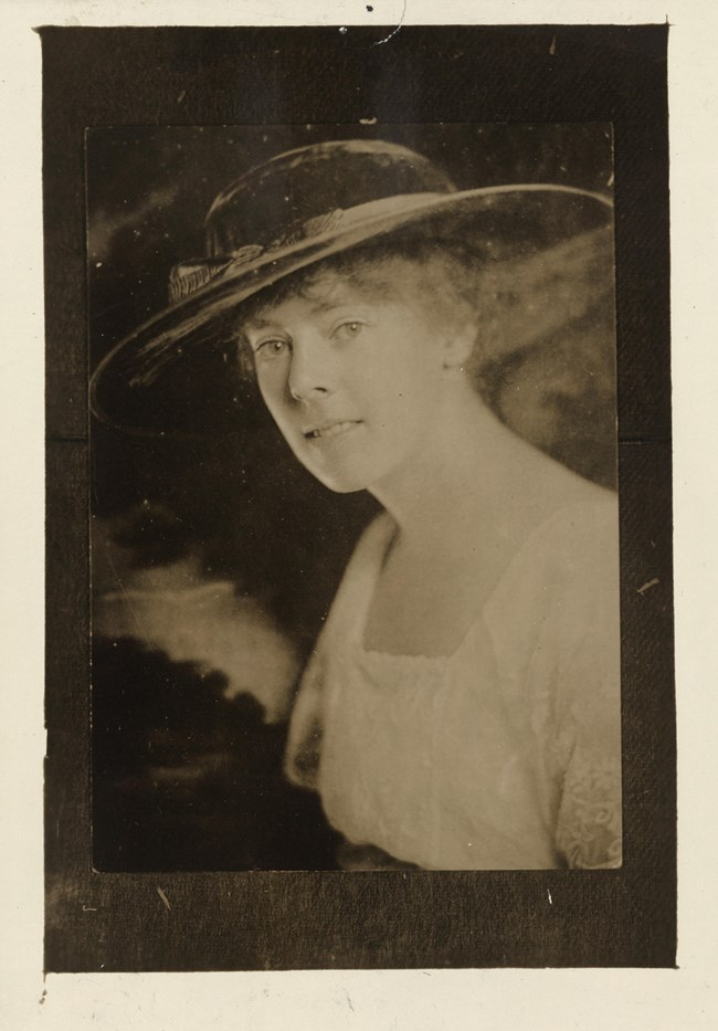 Formal portrait, head and chest, Katherine Morey, facing left with head turned toward camera, wearing wide-brimmed hat.