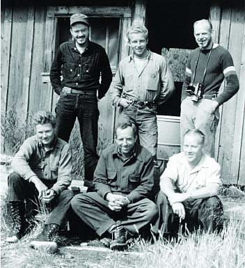 A group of six white men pose in front of an old NPS park building for the Katmai Project.